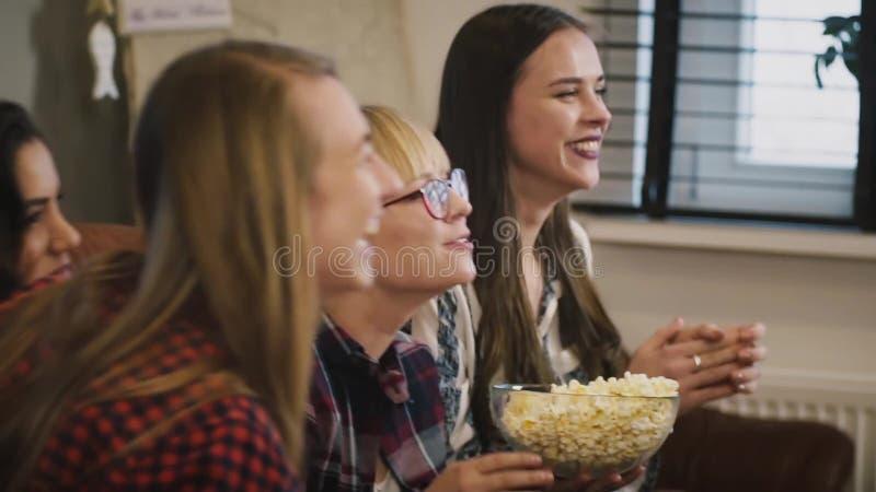 Émission de TV caucasienne heureuse de montre de filles Mouvement lent émotion Belles dames observant le jeu de sports avec le ma clips vidéos