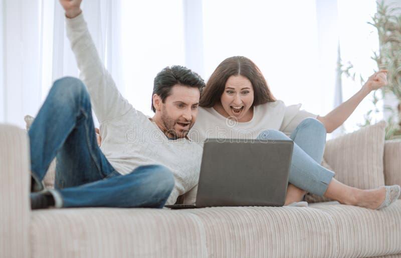 Émission de TV de observation de jeunes couples sur leur ordinateur portable image libre de droits