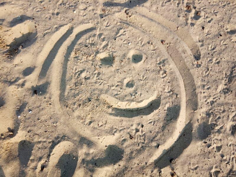 Émoticône peinte sur le sable Physiognomie drôle, visage Sourire sur la plage images libres de droits
