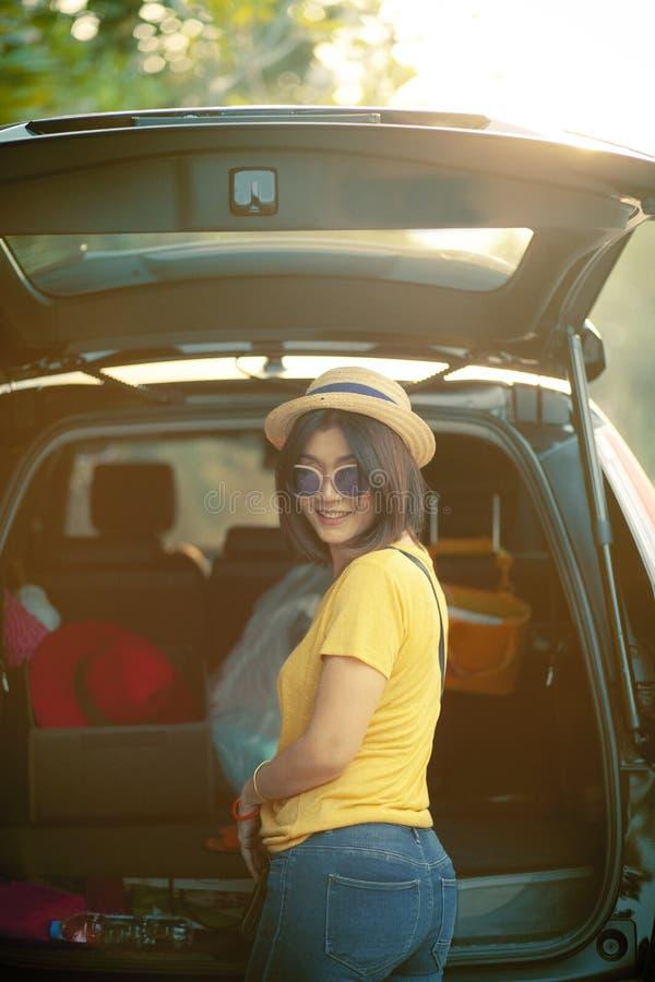 Émotion de sourire toothy de bonheur de femme de voyageur reculant du chargement de voiture de suv appartenant pour le voyage de  photos stock