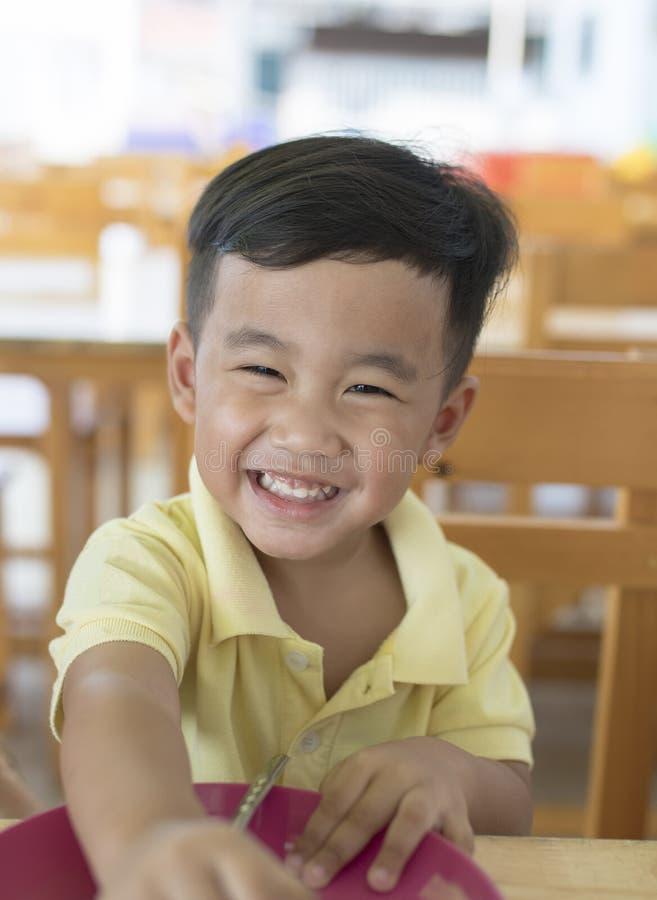 Émotion de sourire Toothy de bonheur de visage de se reposer asiatique d'enfants image libre de droits