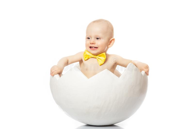 Émotions du ` s d'enfants Portrait de bébé adorable se reposant dans la coquille d'oeufs avec un papillon jaune sur le fond blanc photo stock