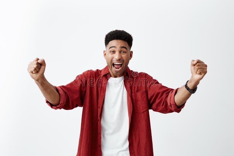 Émotions positives Portrait de jeune homme à la peau foncée heureux avec la coupe de cheveux Afro dans des mains de propagation d image stock