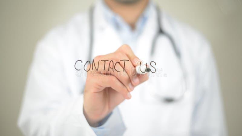 Éntrenos en contacto con, escritura del doctor en la pantalla transparente imagen de archivo