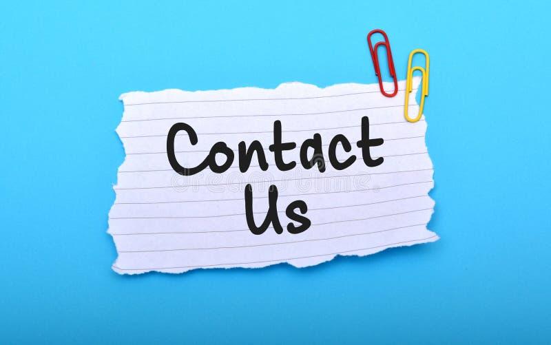 Éntrenos en contacto con mano escrita en el papel con el fondo azul imagen de archivo