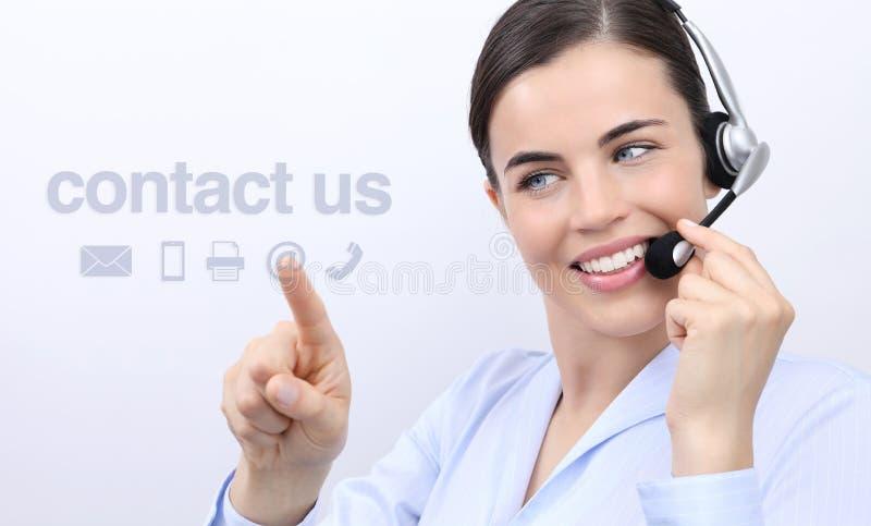 Éntrenos en contacto con, mujer del operador del servicio de atención al cliente con la sonrisa de las auriculares foto de archivo libre de regalías