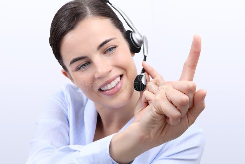 Éntrenos en contacto con, mujer del operador del servicio de atención al cliente con las auriculares imagen de archivo