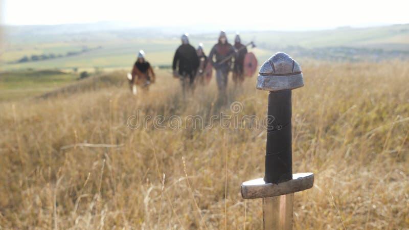 Épée collant dans la terre sur le backgrond de Vikings allants image stock