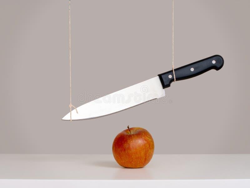 Épée de menace de Damocles, concept de risque, métaphore - grand couteau attaché et suspendu au-dessus de la pomme Dur?e toujours images libres de droits