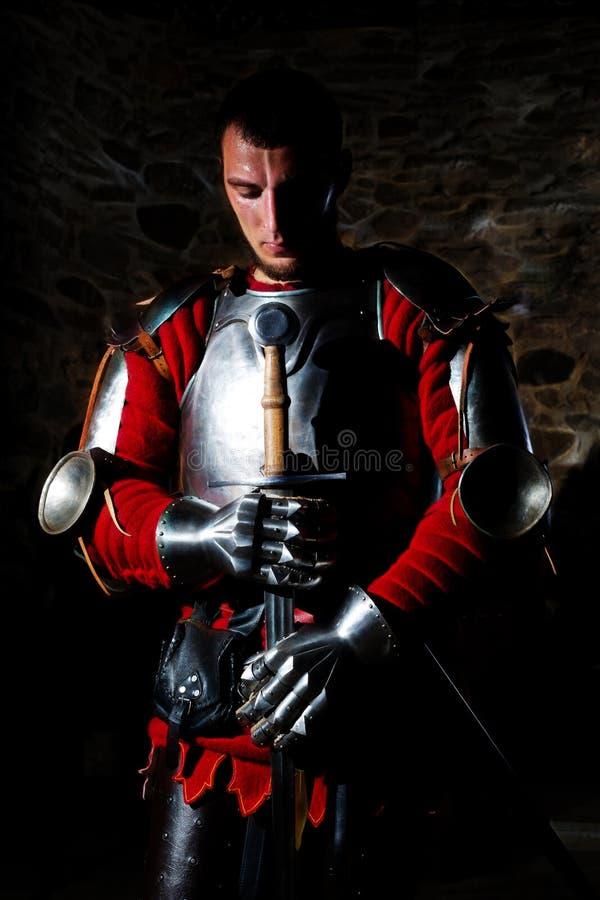 Épée de Standing With Metal de chevalier et avec la tête cintrée dans la prière images stock