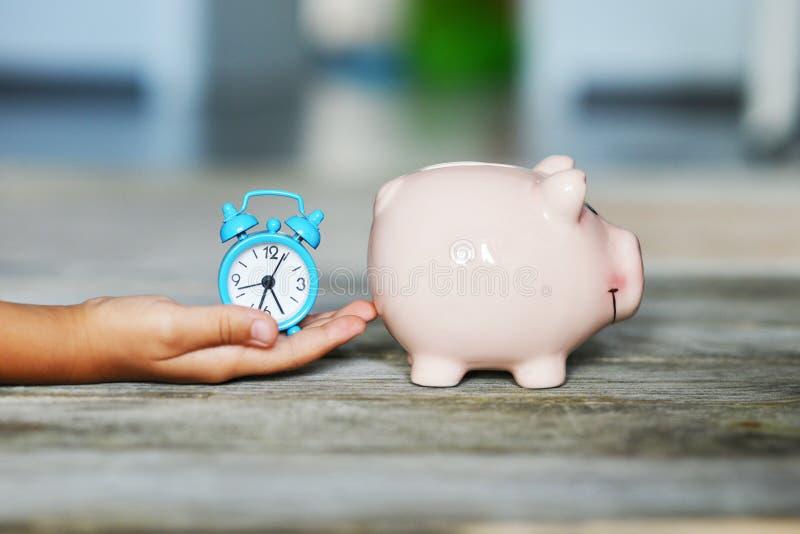 Épargnez l'heure pour l'instant précieux avec votre concept d'enfant, tirelire et réveil dans la main de kid's photographie stock libre de droits