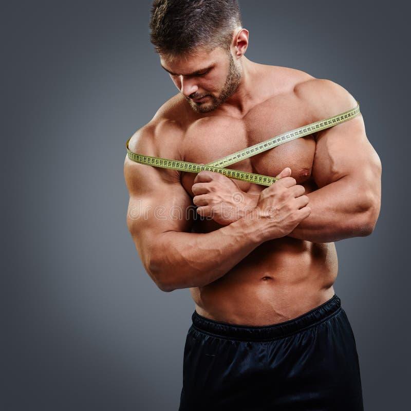 Épaules de mesure de Bodybuilder avec le ruban métrique photographie stock libre de droits