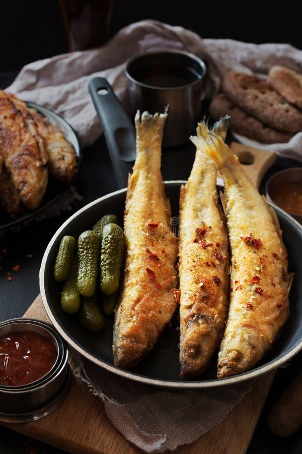 Éperlan frit sur une casserole foncée avec de la sauce photo libre de droits