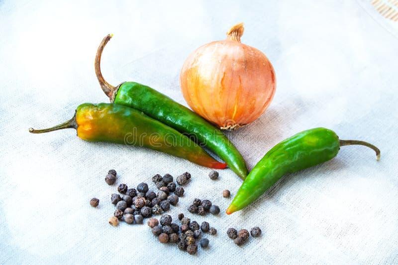 ?pice le poivre noir et les poivrons verts chauds aux oignons sur un tissu de toile sur la cuisine photo stock