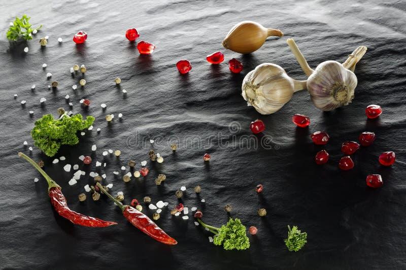 épice Plan rapproché de poivre de piment, de poivrons noirs, blancs et rouges, de sel, de persil, d'ail, d'oignon et de grenade photo libre de droits