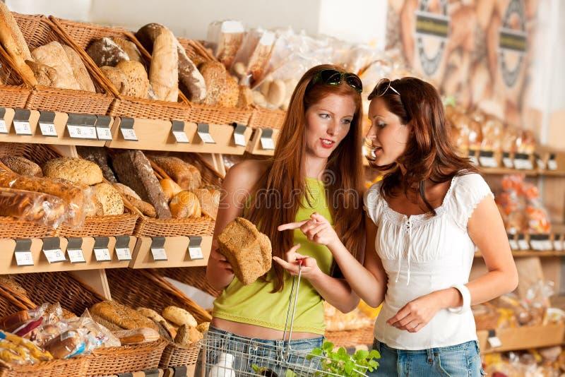Épicerie : Deux femmes choisissant le pain photographie stock libre de droits