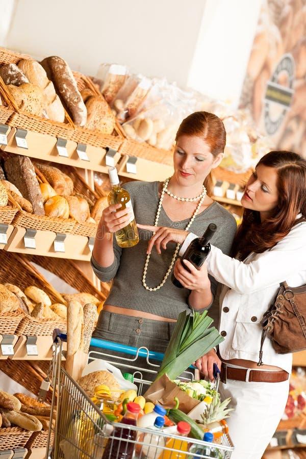 Épicerie : Deux jeunes femmes choisissant le vin image stock