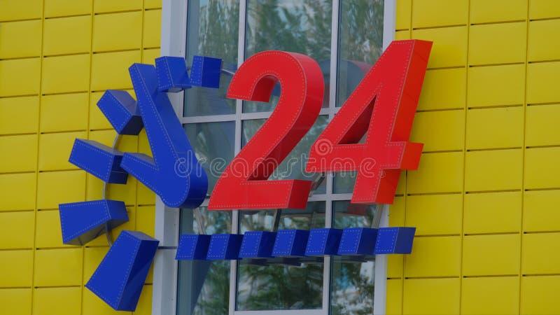 Épicerie jaune avec une horloge bleue et de grands numéros rouges 24 services d'heure photo stock