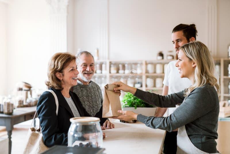 Épiceries de achat de couples supérieurs dans le magasin de rebut zéro, assistants de ventes les servant photographie stock
