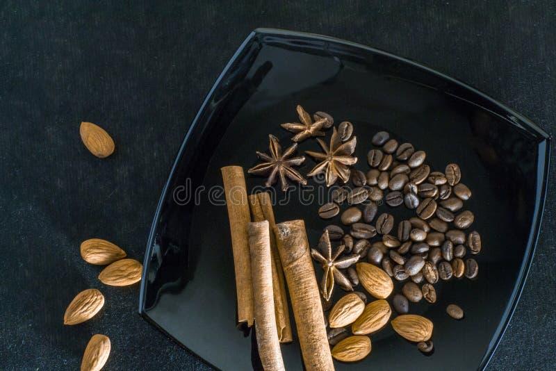 Épices aromatiques avec des grains de café et des amandes sur un fond noir image libre de droits