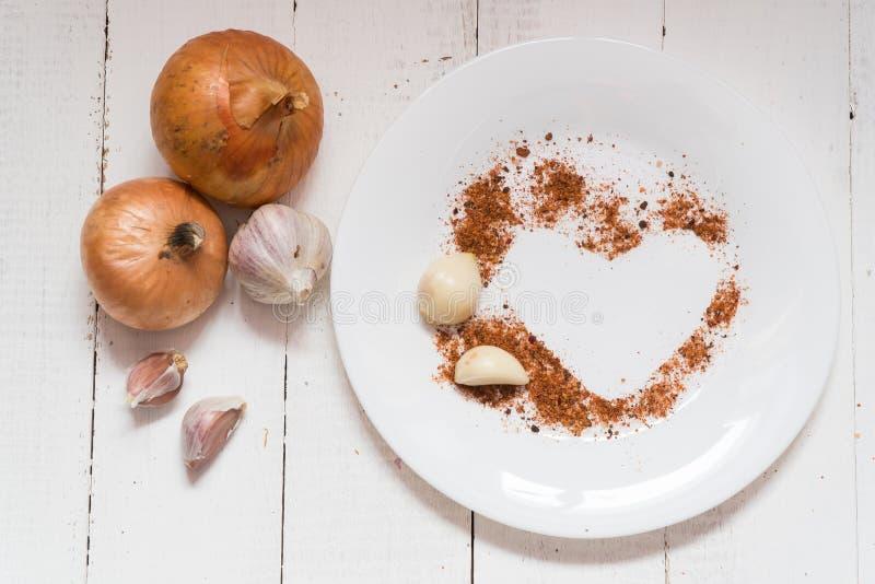 Épices d'un plat épices de poivre d'oignon d'ail sous forme de coeur photo stock