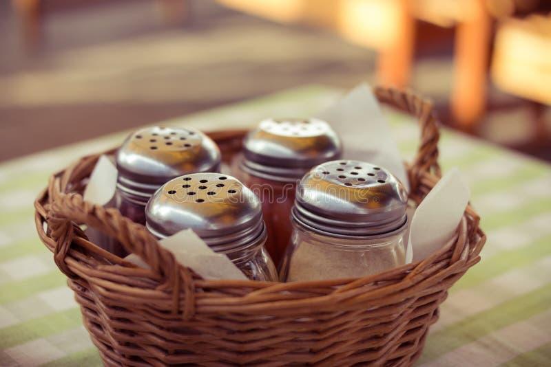 Épices dans des bouteilles en verre dans un panier en osier sur la table en café images libres de droits