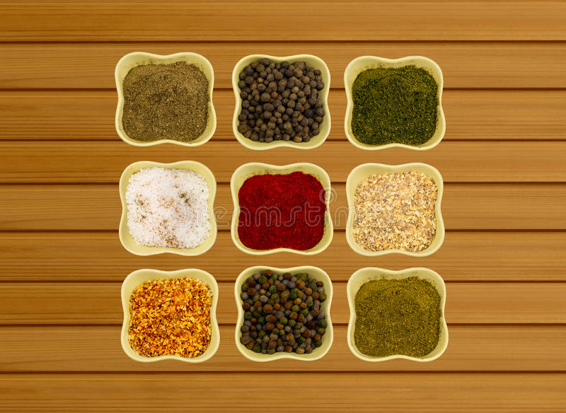 Épices dans des cuvettes en céramique sur un fenouil et une coriandre parfumés de paprika de paprika de fond en bois photographie stock