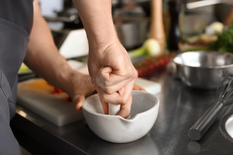 Épices de broyage d'homme en mortier pendant les cours de cuisine photographie stock libre de droits