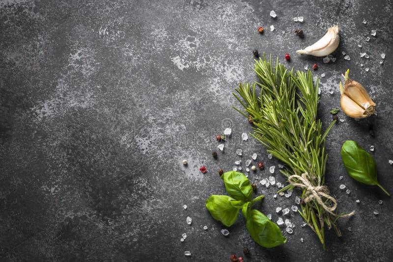 Épices et herbes au-dessus de table en pierre noire image libre de droits