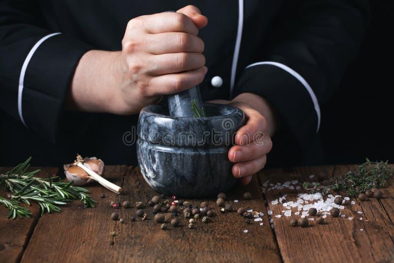 Épices et herbes de broyage de chef de femme en mortier pour la nourriture faisant cuire sur un fond noir images libres de droits