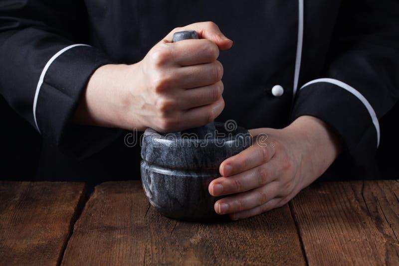 Épices et herbes de broyage de chef de femme en mortier pour la nourriture faisant cuire sur un fond noir image libre de droits