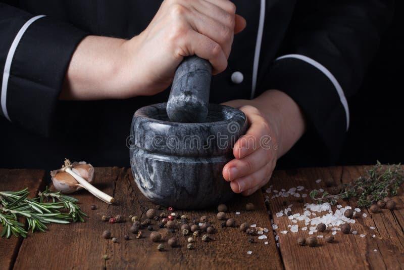 Épices et herbes de broyage de chef de femme en mortier pour la nourriture faisant cuire sur un fond noir photographie stock libre de droits