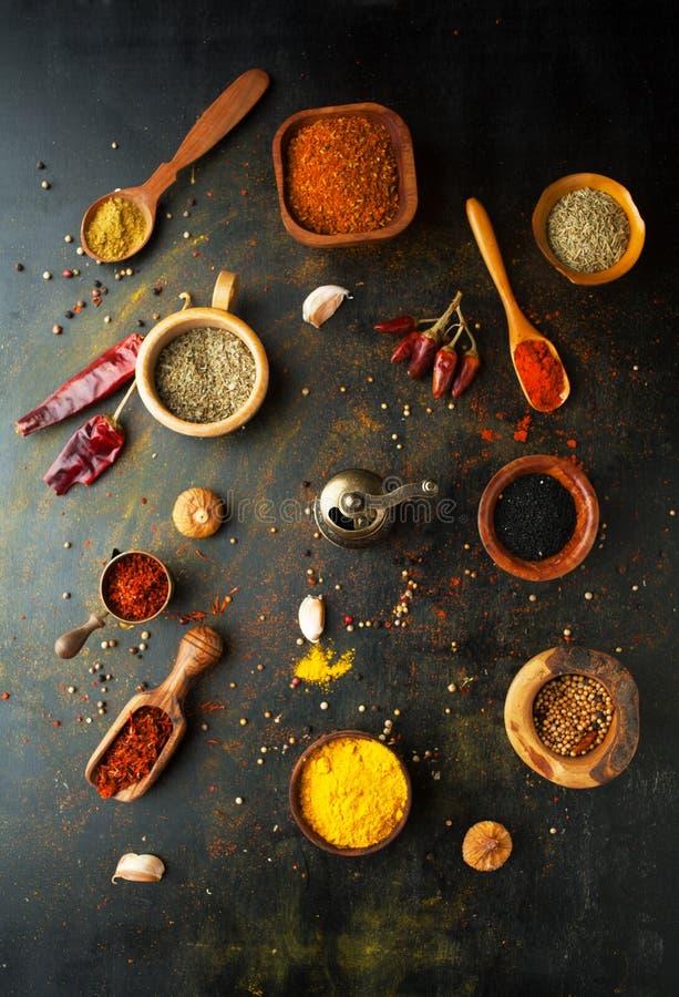 Épices, herbes et condiments sur une table dans une cuillère sur un Ba foncé photographie stock