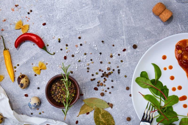 Épices italiennes Bol de poivre noir, de piments et de romarin Salade à côté d'un repas de haricot sur un fond de table Copiez l' image stock