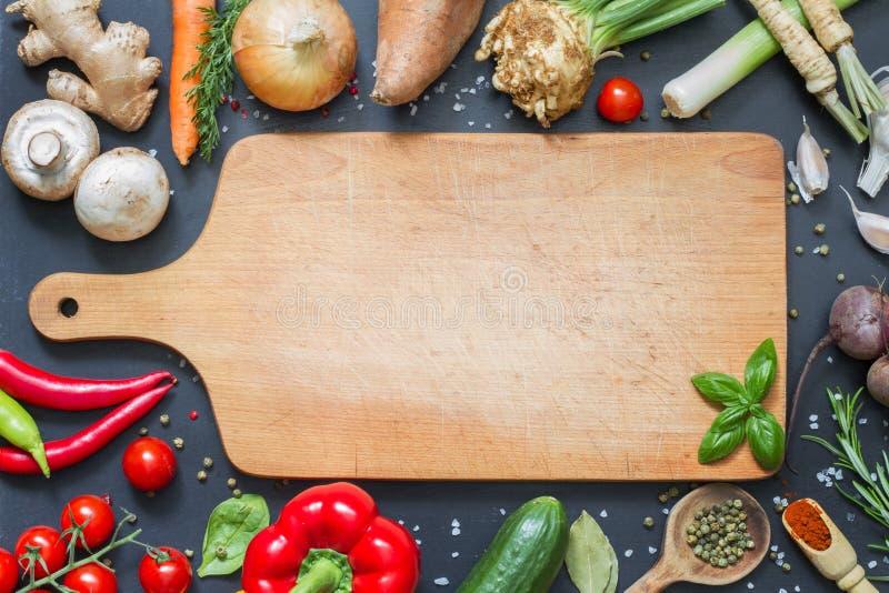 Épicez les herbes et le fond de nourriture de légumes et la planche à découper vide photographie stock