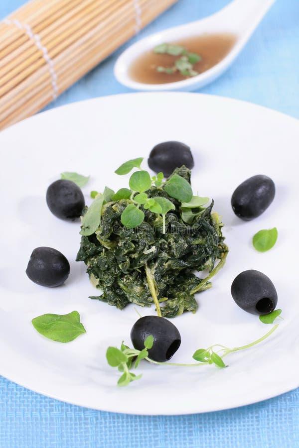 Épinards avec les olives noires image stock