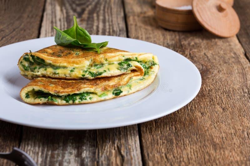 Épinards de bébé et omelette de parmesan, petit déjeuner végétarien sain images libres de droits
