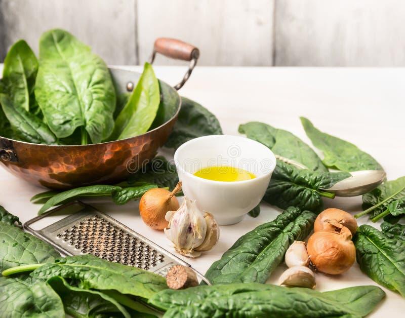 Épinards frais dans la vieille casserole de cuivre avec la cuvette d'huile et la râpe de noix de muscade, préparation photographie stock
