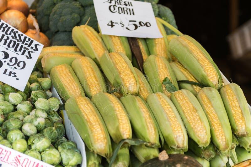 Épis de maïs et choux de bruxelles à une stalle au marché de place de Pike de Seattle photographie stock libre de droits
