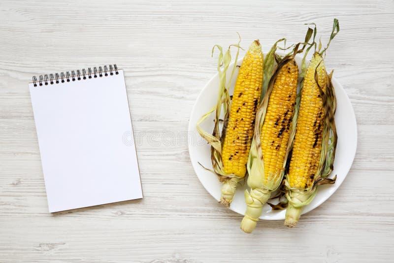 Épis de maïs grillés d'un plat rond et d'un bloc-notes vide au-dessus de la table en bois blanche, vue supérieure photos libres de droits