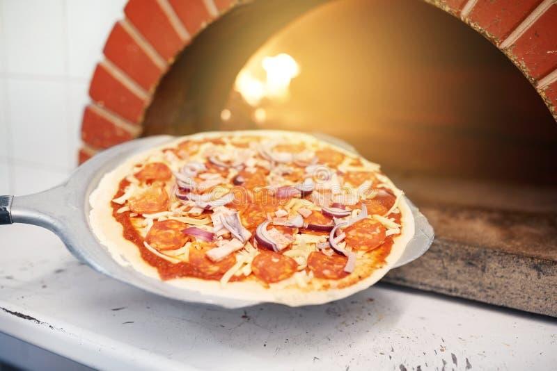 Épluchez placer la pizza dans le four à la pizzeria photos stock