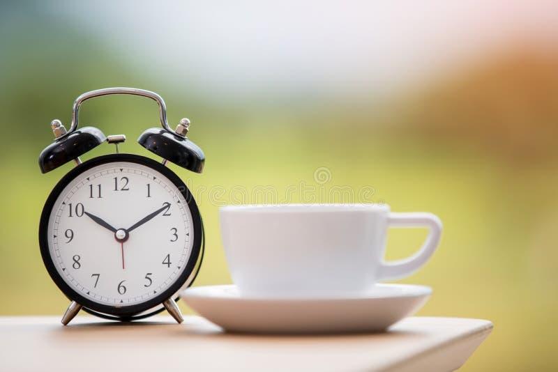 Épocas del café con el despertador en la tabla imagenes de archivo