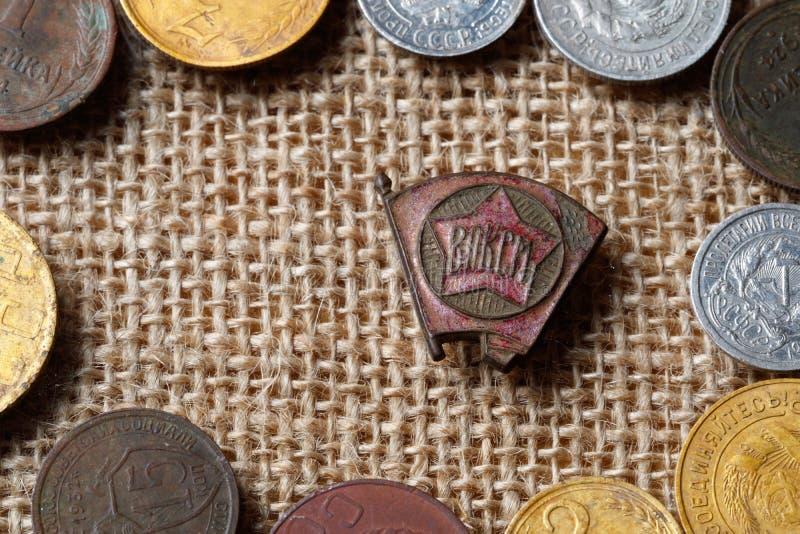 Épocas do ícone de URSS do Komsomol cercado por moedas soviéticas fotografia de stock royalty free