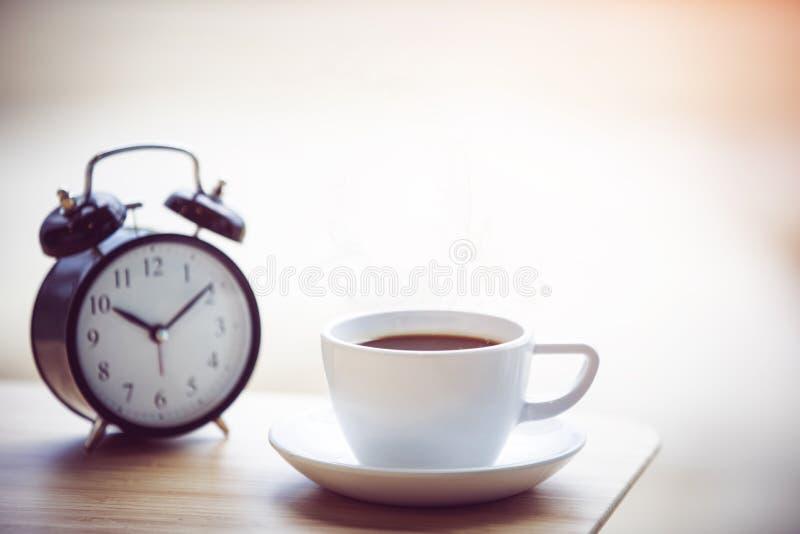 Épocas do café com o despertador na tabela foto de stock