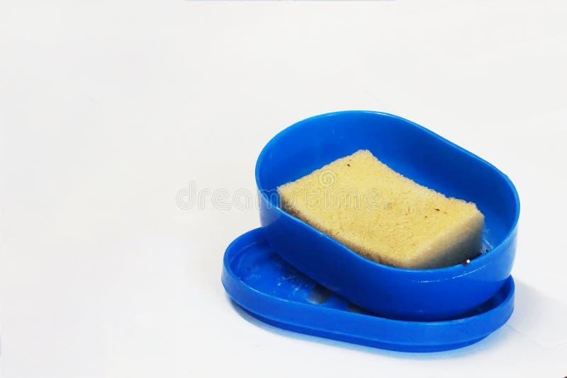 Éponge jaunâtre de lavage de plat dans la boîte bleue photo stock