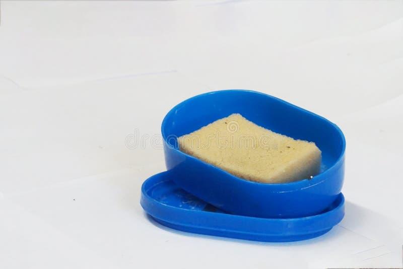 Éponge jaunâtre de lavage de plat dans la boîte bleue photos stock