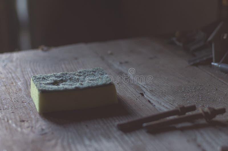 Éponge pour nettoyer dans un vieil atelier abandonné Dessus de table en bois, vis photos libres de droits