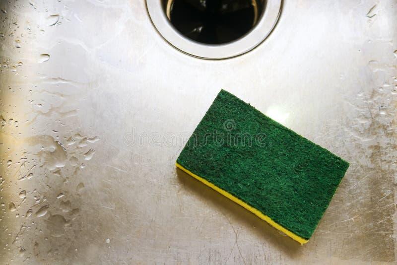 Éponge scrubing verte et jaune se situant dans l'éraflure et l'évier humide avec la disposition de garage photographie stock