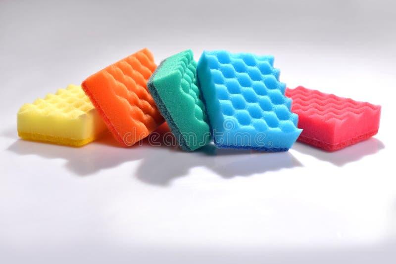 Éponges multicolores pour les plats de lavage sur le fond blanc images libres de droits