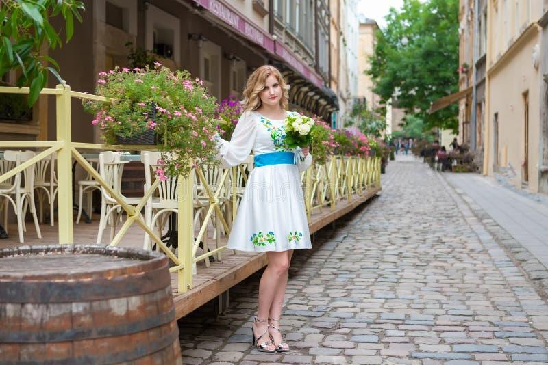 Épousant, belle fille avec un bouquet de mariage posant près de la barrière de fleur à Lviv photographie stock